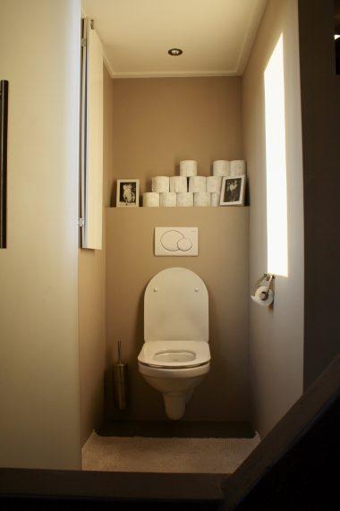Toilet afgescheiden door achterzijde douche en melkglas deur.